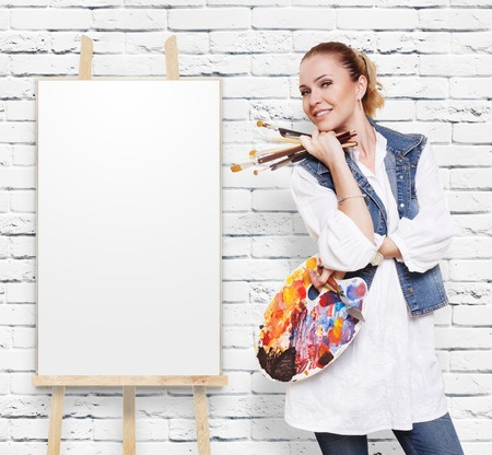 fine art: Happy artist. Woman artist with art tools. Girl painter with brushes and palette. Empty canvas at easel at white brick wall with copy space. Fine art. Art classes for adults, education concept.