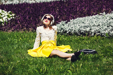 day break: Student girl or young woman listens to the music from tablet pc outdoors. Girl in earphones wears sunglasses sitting on the grass in the park. Music leisure. Having fun, rest, relax in park. Stock Photo