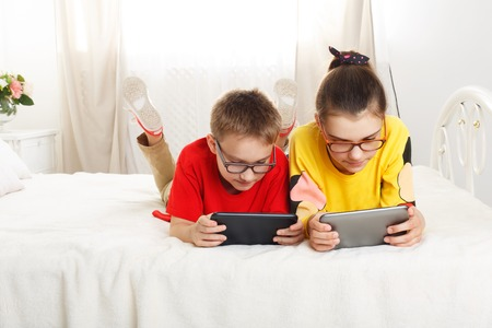 Two children, siblings on parents bed at morning with tablets. Brother and sister play computer games. Siblings and gadgets. Children in glasses. Girl and boy play at device Stock Photo