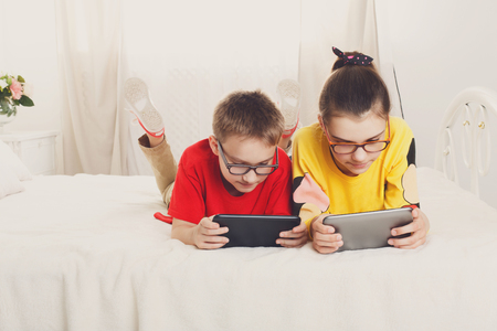 gamers: Two children, siblings on parents bed at morning with tablets. Brother and sister play computer games. Siblings and gadgets. Children in glasses. Girl and boy play at device Stock Photo