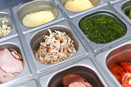 with fillings: Sandwich bar salads choice in metal containers. Different fillings - chicken meat, sliced ham, tomatoes, fresh herbs for preparing fast food take away in cafe. Vendors equipment for street meal. Stock Photo