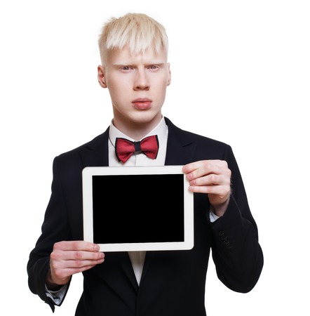 cute guy: Albino young man portrait with tablet. Blond pale guy in suit with red bow tie isolated at white background. Stylish male person shows computer device with copy space at black screen Stock Photo