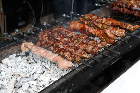 chicken chop: Raw kebab grilling on metal skewer. Raw meat roasting at barbecue. BBQ fresh beef and chicken chop slices. Traditional eastern dish, shish kebab. Grill on charcoal and flame, picnic, street food