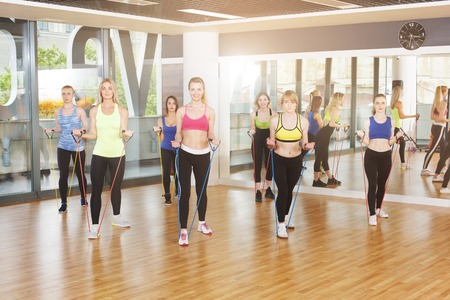 lower body: Group of young women in fitness class making exercises. Girls training with resistance band. Healthy lifestyle in sport club, training with lower body crossfit expander. Stock Photo