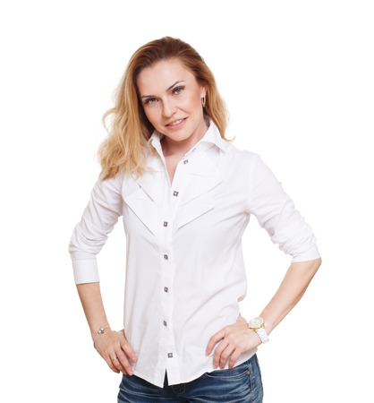 self confident: Cheerful caucasian lady posing in white shirt isolated at white background. Blond middle-aged attractive woman looking at camera, self confident and smiling. Stock Photo