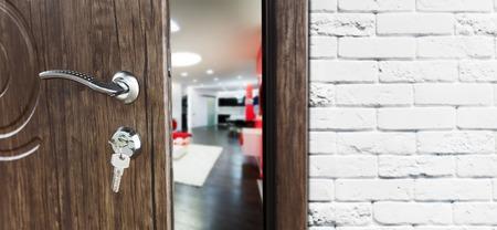 La moitié ouvrait la porte dans un salon. Poignée de porte, serrure de porte. Porte du salon à moitié ouverte. Ouverture de la porte. Bienvenue, concept de confidentialité. Entrée dans la pièce. Porte au mur en briques blanches, design d'intérieur moderne.