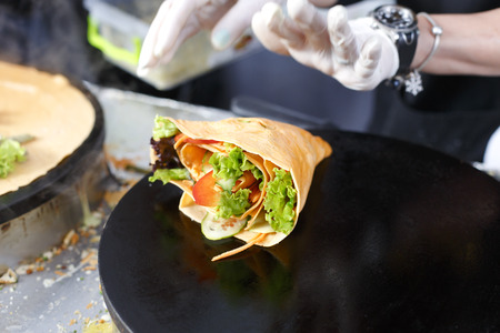 salty: Making vegetable crepe, roll with tomatoes and lettuce. Salty crepe or pancake with fillings made by street vendors hands at outdoors creperie. French cuisine, cooking for commercial kitchen.