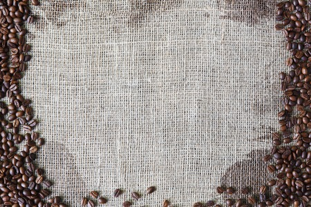 sack cloth: Burlap texture with coffee beans border. Sack cloth background. Brown natural sackcloth canvas with frame and copy space. Seeds at hessian textile