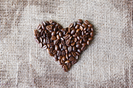 sack cloth: Burlap texture with coffee beans heart shape background, love symbol. Sack cloth canvas with copy space. Seeds at hessian textile Stock Photo