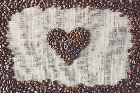 sack cloth: Burlap texture with coffee beans heart shape background, love symbol. Sack cloth canvas with copy space. Frame of seeds at hessian textile