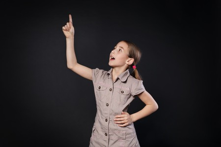 eureka: Small girl has an idea. Child shows finger up as an eureka, inspiration sign. Smart schoolgirl studio portrait at black background, school study and getting knowledge concept. Stock Photo