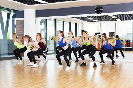 Fitness workout. Group of young women in sport club making exercises. Girls do squats with barbells. Healthy lifestyle in club, training with weights. Stock Photo