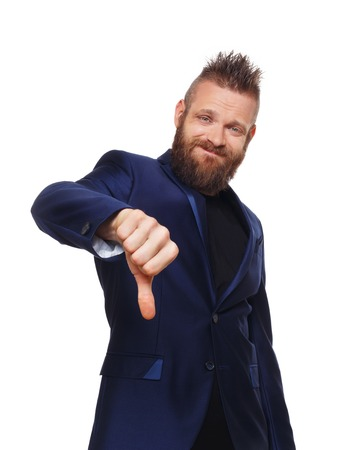 disapproving: Man gesturing thumb down sign isolated at white. Young stylish hipster with beard in blue suit showing negative emotion. Sarcastic male portrait symbolising loss and failure, disapproving something.