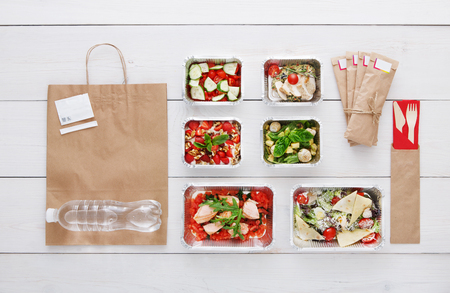 eat right: Healthy food delivery. Take away of natural organic low carb diet. Eat right concept, fitness nutrition in foil boxes, water bottle, cutlery and brown paper package. Top view, flat lay at white wood