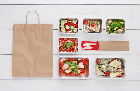 eat right: Healthy food delivery. Take away of natural organic low carb diet. Fitness nutrition in foil boxes, cutlery and brown paper package with copy space. Top view, flat lay at white wood