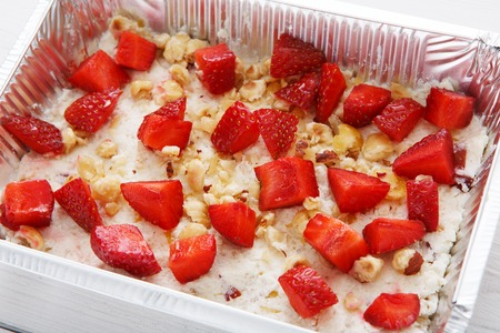 eat right: Healthy eating, diet concept. Natural dessert. Take away organic food in foil box. Oatmeal porridge with strawberries and nuts closeup Stock Photo