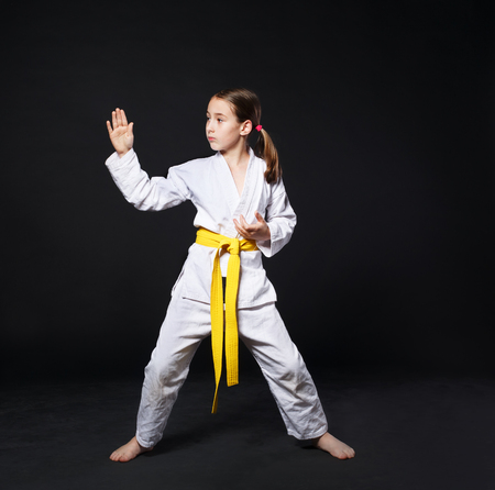 girl fight: Little girl in karate suit kimono in studio at black background. Female child shows judo or karate stans in white uniform with yellow belt. Individual martial art sport for kids. Full body portrait