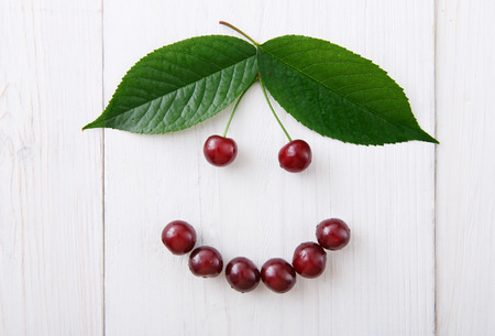 green smiley face: Smiley face from sweet fresh cherries with green leaves. Smile sign from healthy food. Fruits closeup on white rustic wood pattern.