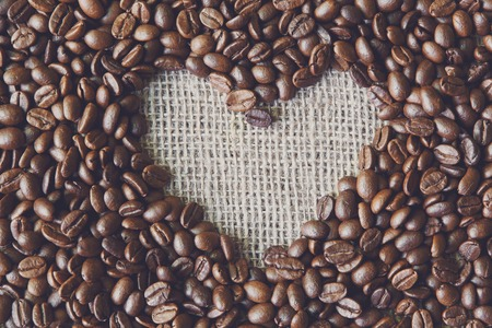 sack cloth: Plenty of coffee beans and burlap texture heart shape background, love symbol. Sack cloth canvas with copy space. Seeds at hessian textile