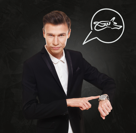 thinking cloud: Time to fly. Businessman point at his watch showing time is money concept. Man in suit with clock at black background, thinking cloud with plane sign. Flight departure, late at business trip. Stock Photo