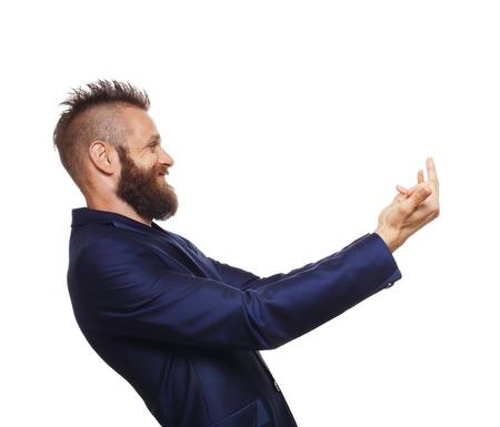 irrespeto: Vista lateral retrato de hombre joven con barba, reír, muestran el dedo medio, aislado en fondo blanco. Hombre emocional encontrar ridícula, falta de respeto y humilla a alguien Foto de archivo