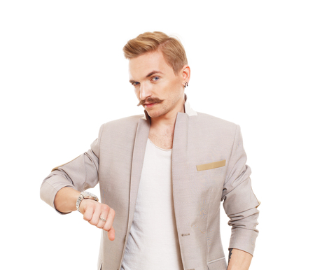 sarcastic: Man gesturing thumb down sign isolated at white. Young stylish guy with mustache in suit showing negative emotion. Sarcastic male portrait symbolising loss and failure, disapproving something.