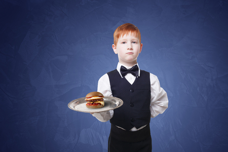servant: Little waiter stands with tray serving hamburger. Redhead child boy in suit plays restaurant servant, gives burger at blue background