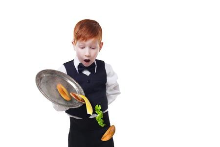 maldestro: Clumsy piccolo cameriere scende cibo da vassoio da portata hamburger. Cheeseburger caduta con condimenti separati. Dropping strati hamburger. Redhead bambino in un fallimento completo, isolato a sfondo bianco Archivio Fotografico