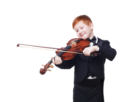 ruffian: Cute redhead child plays violin isolated at white background. Red-haired charming boy musician in tailcoat or tuxedo smile. Classical music study concept Stock Photo