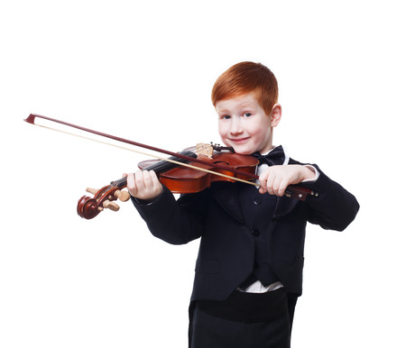 ruffian: Cute redhead child plays violin isolated at white background. Red-haired charming boy musician in tailcoat or tuxedo. Classical music study concept