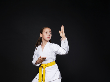 female person: Little girl in karate suit kimono in studio at black background. Female child shows judo or karate stans in white uniform with yellow belt. Individual martial art sport for kids. Waist up portrait Stock Photo