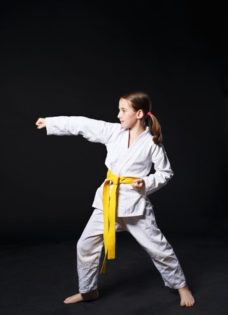 female clothing: Little girl in karate suit kimono in studio at black background. Female child shows judo or karate stans in white uniform with yellow belt. Individual martial art sport for kids. Full body portrait