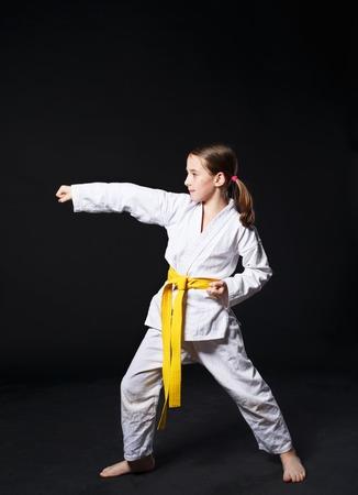 mujer deportista: Niña en traje de karate kimono en estudio en el fondo negro. Infantil femenina muestra de judo o karate stans en el uniforme blanco con cinturón amarillo. Persona deporte de artes marciales para los niños. Retrato de cuerpo entero