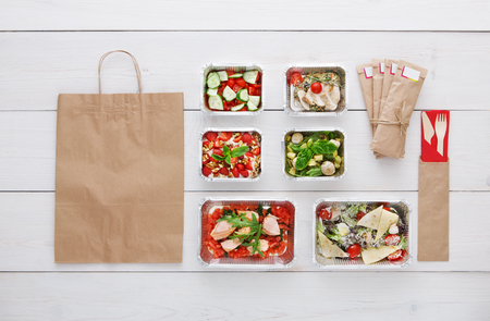 eat right: Healthy food delivery. Take away of natural organic low carb diet. Fitness nutrition in foil boxes, water bottle, cutlery and brown paper package with copy space. Top view, flat lay at white wood Stock Photo