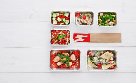 low carb diet: Healthy food delivery. Take away of natural organic low carb diet. Fitness nutrition in foil boxes, cutlery in brown paper package. Top view, flat lay with copy space at white wood