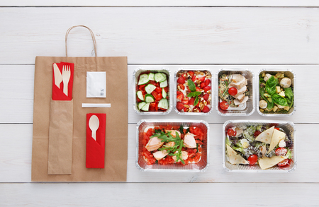carb: Healthy food delivery. Take away of natural organic low carb diet. Fitness nutrition in foil boxes, cutlery and brown paper package. Top view, flat lay at white wood