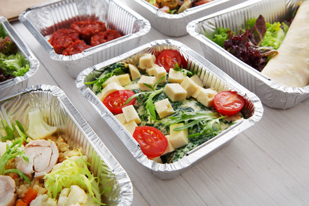 eat right: Healthy eating, diet concept. Take away organic food. Weight loss nutrition in foil boxes. Vegetables and omelette with cherry tomatoes, spinach and cheese at white wood Stock Photo