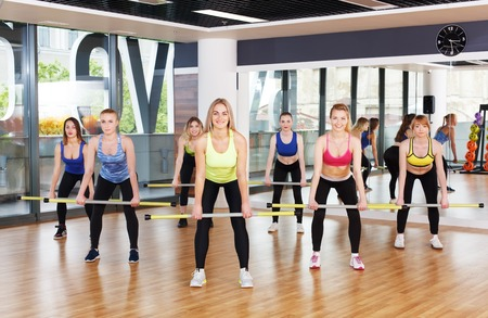 Deadlift with light weight. Group of young women in fitness class making exercises. Girls do squats with barbells. Healthy lifestyle in fitness club, weight loss training Stock Photo - 59483566