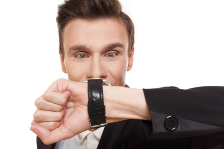 disturbed: Time is money. Closeup portrait of businessman look at his watch disturbed, show that it is late, hurry up, check the time. Man in suit isolated at white background. Stock Photo