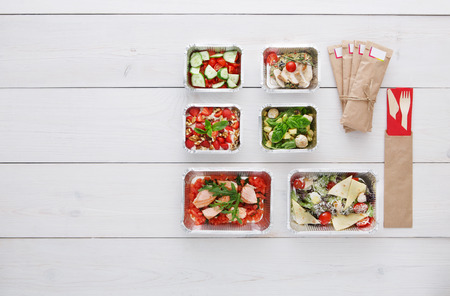 carb: Healthy food delivery. Take away of natural organic low carb diet. Fitness nutrition in foil boxes, cutlery in brown paper package. Top view, flat lay with copy space at white wood