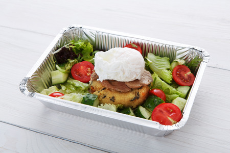 medium closeup: Restaurant food delivery in foil box on white wood table. Poached egg closeup on veil steak medium rare with fresh vegetable salad and couscous cushion. Dish take away closeup, healthy meal.