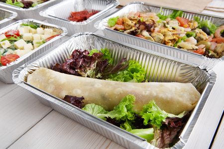 foil roll: Healthy eating, diet concept. Take away organic food. Weight loss nutrition in foil boxes. French crepe roll with vegetable filling and lettuce at white wood