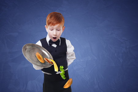clumsy: Clumsy little waiter drops food from tray serving hamburger. Cheeseburger falling with separated toppings. Dropping burger layers. Redhead child boy in suit, failure at blue background