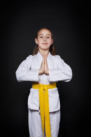 waist up: Little girl in karate suit kimono in studio at black background. Female child shows judo or karate stans in white uniform with yellow belt. Individual martial art sport for kids. Waist up portrait Stock Photo