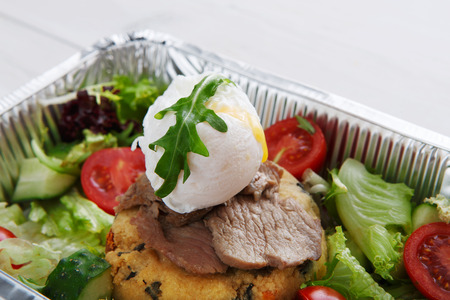 medium closeup: Restaurant food delivery in foil box. Poached egg closeup on veil steak medium rare with fresh vegetable salad and couscous cushion. Dish take away closeup, healthy meal.