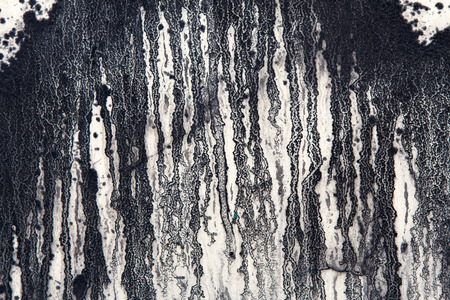paint drips: White concrete wall with black paint drips, drops and stains. Abstract background, rough grunge texture, dirty and messy old urban wall surface. Stock Photo
