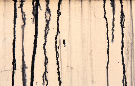 paint drips: Beige pastel concrete wall with black paint drips, drops and stains. Abstract background, rough grunge texture, dirty and messy old urban wall surface. Stock Photo