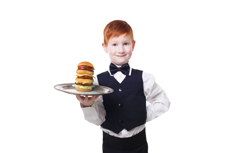 servant: Little waiter stands with tray serving big double hamburger. Smiling redhead child boy in suit plays restaurant servant, gives burger isolated at white background Stock Photo