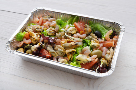 eat right: Healthy food take away, diet concept. Organic nutrition. Weight loss dish in foil box. Vegetarian seafood salad with mussels, shrimp, tomatoes, olives and grapefruit at white wood Stock Photo