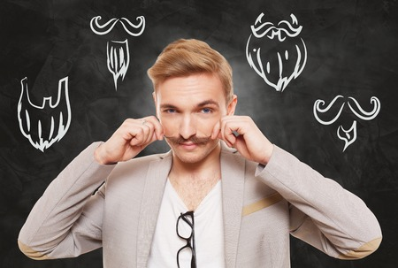haircuts: Man choose facial hair style, beard or mustache. Barber shop haircuts choice. Male fashion, various beard styles drawings at blackboard. Stylish young guy think of changing hairstyle. Man portrait